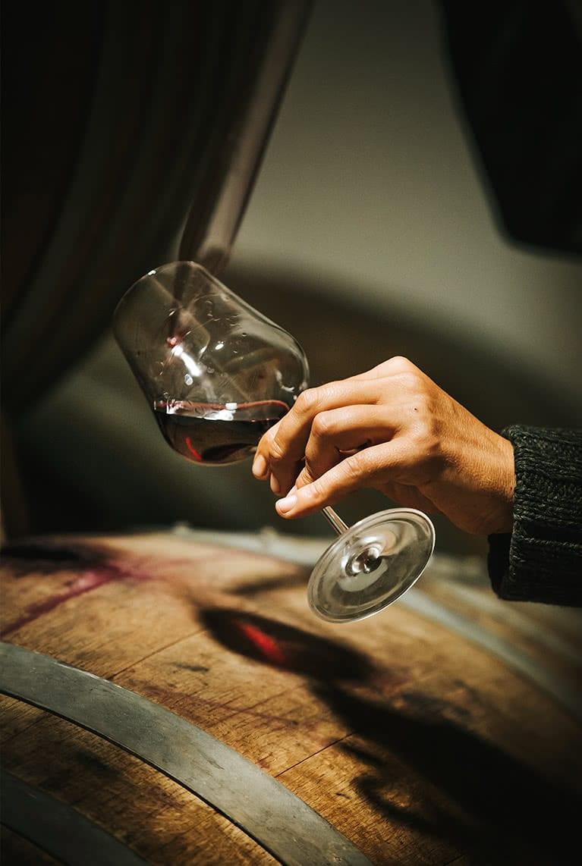 Mano sujetando copa de vino, sirviendo un Vino Tinto directo de la barrica