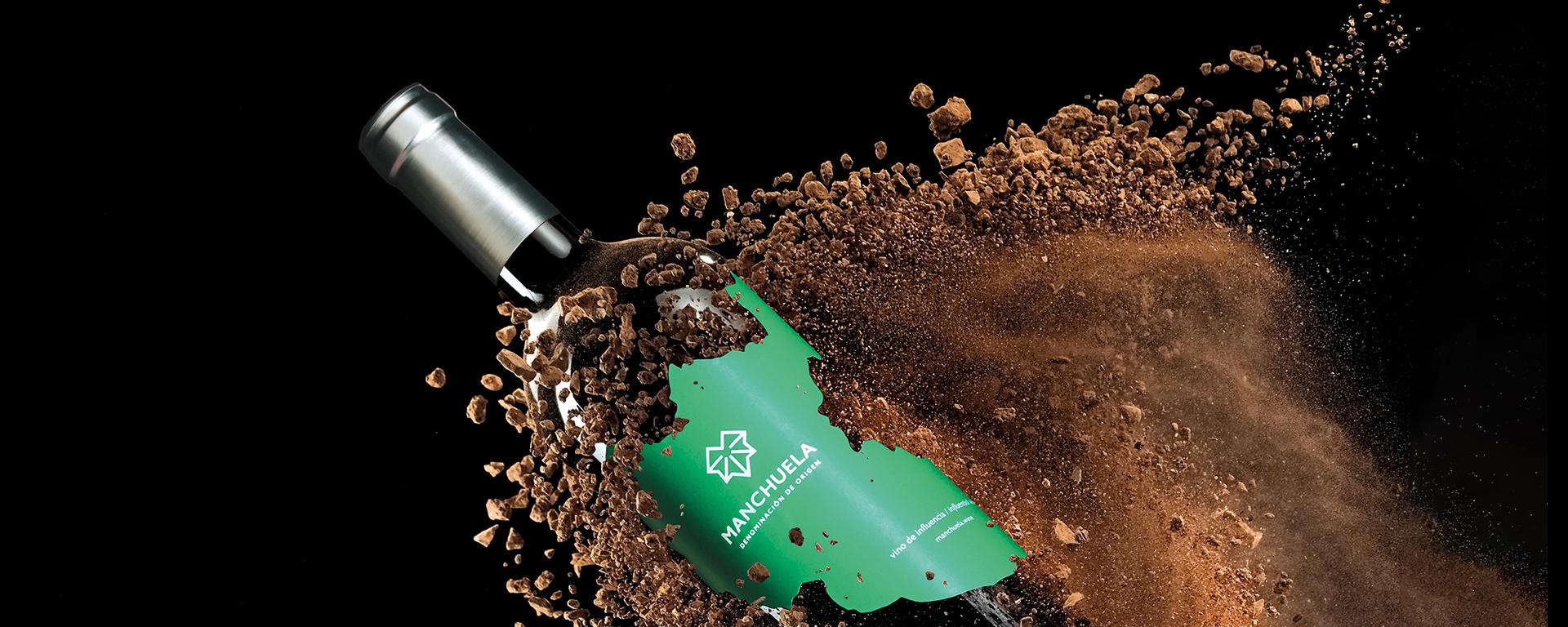 Botella de vino de la Denominación de Origen Manchuela saliendo de la tierra